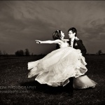 Wedding couple swirling in field