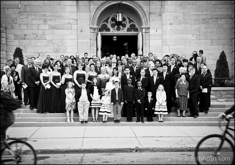 Wedding group shot with bicycles passing