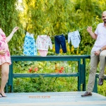 Couple holding baby clothes during maternity session